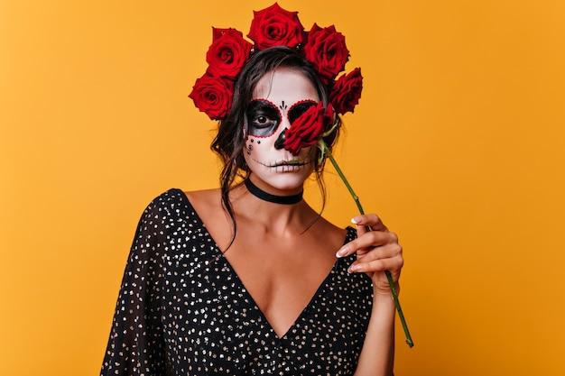 De sensuele mexicaanse meisjesholding nam op gele muur toe. triest vrouwelijke zombie poseren met bloem in halloween.