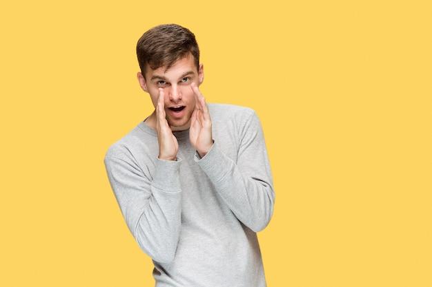 De serieuze jongeman kijkt voorzichtig op gele studio en spreekt geheim voor de camera