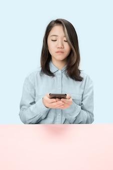 De serieuze zaken vrouw zitten en kijken naar telefoon tegen blauwe achtergrond.