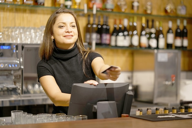 De serveerster bij de kassa