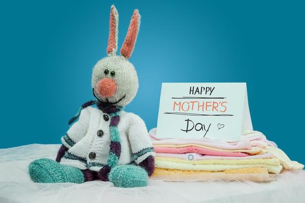 De set babyartikelen in de stapel, speelgoed en blanco kaart op een blauwe achtergrond. gelukkig moederdag concept