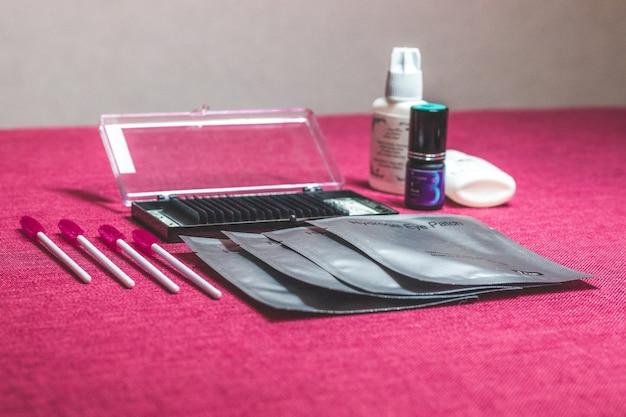De set hulpmiddelen voor ogen. cosmetische apparatuur bestaat uit wimperborstels, mascara, krultang en valse wimpers.