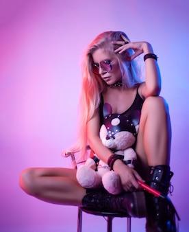 De sexy blondine met lang haar speelt met een speelgoedbeer in bdsm-accessoires en een zweep