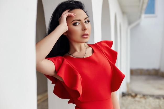 De sexy donkerbruine vrouw in rode kleding bevindt zich dichtbij de muren van de oude villa's door het overzees. portret van een meisjesclose-up, romantische seksuele manier. haar kronkelde in de wind. zomer, vakantie, reizen