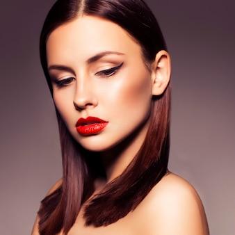De sexy donkerbruine vrouw met kattenogen en rode lippen maakt omhoog op een neutrale donkere achtergrond. onberispelijke huid