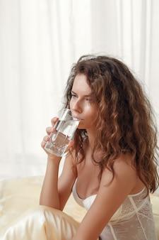 De sexy krullende slanke kaukasische meisjeszitting in een ochtendbed houdt een glas water