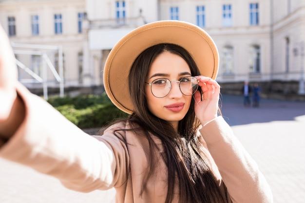 De sexy modelvrouw maakt in openlucht selfie op haar nieuwe smartphone in de stad in zonnige dag