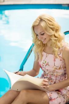 De sexy slanke schitterende jonge blonde leest het menu van het poolrestaurant in luxehotel