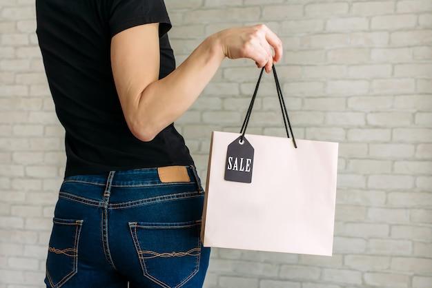 De sexy vrouw in de papieren zak van de denimholding met markering in haar dient het wandelgalerij in. black friday-verkoopconcept.