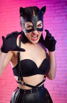 De sexy vrouw in leren kattenmasker op leren riemen en bdsm-riemen grijnst als een kat
