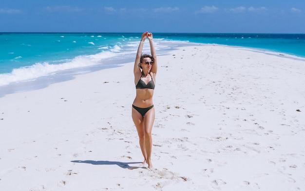 De sexy vrouw zwemt binnen slijtage die zich op zand door de oceaan bevinden