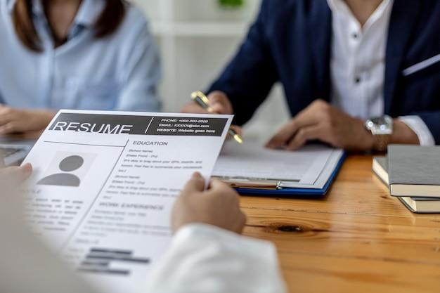 De sfeer van de interviewruimte in het startende bedrijf, de sollicitant overhandigt het cv aan de interviewer als ondersteunend document voor het interview, twee interviewers. sollicitatiegesprek concept