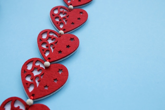 De sfeer van tederheid en liefde. symbolen van valentijnsdag. rode harten op blauwe muur. copyplace, ruimte