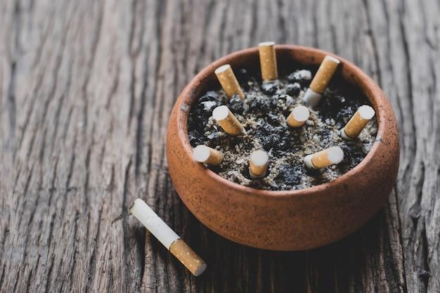De sigarettenpeuk in de pot wordt op een oude houten vloer geplaatst, world no tobacco day-concept.