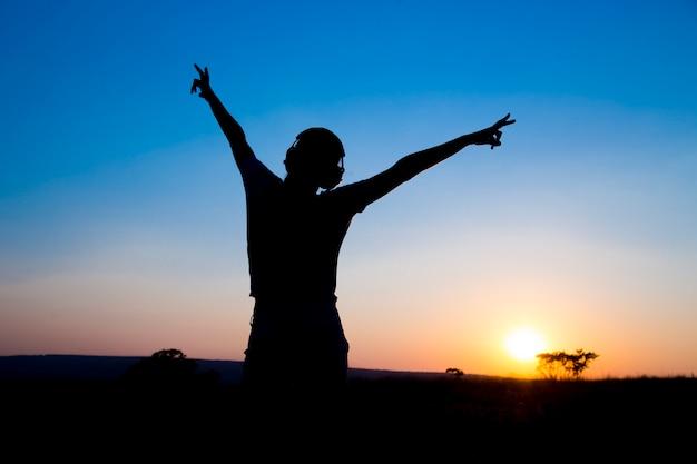 De silhouet jonge vrouw met hoofdtelefoon bij zonsondergang