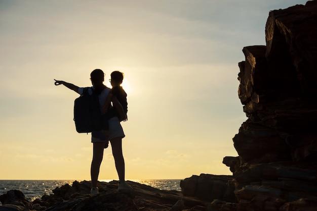 De silhouetfamilie geniet van zonsondergang en overzees