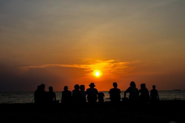 De silhouetfamilie zit en kijkt zonsondergang op strand