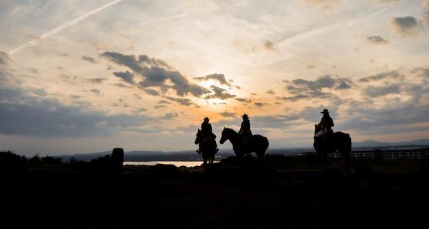 De silhouetfoto van is vrouwen die op zonsondergang voor activiteitenreis paardrijden