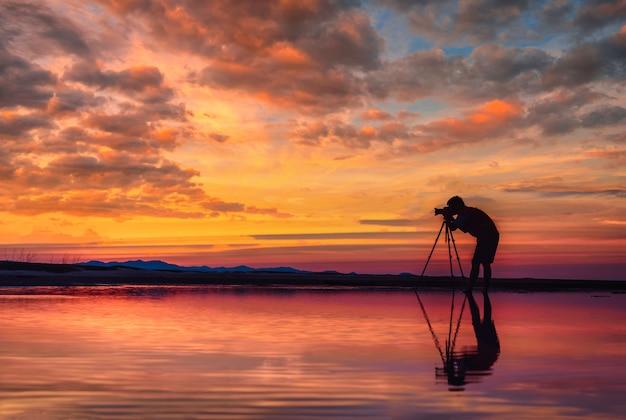 De silhouetfotograaf neemt foto mooi zeegezicht bij zonsondergang in thailand.
