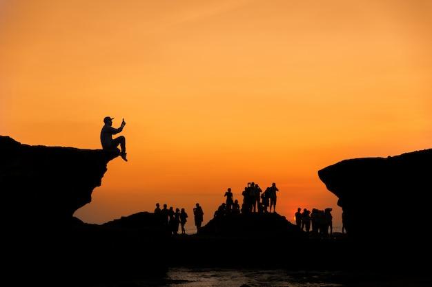 De silhouetgroep mensen neemt foto in zonsondergangtijd tussen de rotsklip