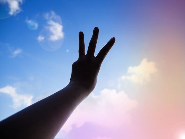 De silhouethand toont drie vingers in de lucht