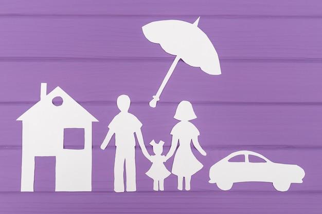 De silhouetten gesneden uit papier van man en vrouw met een meisje onder de paraplu, huis en auto in de buurt