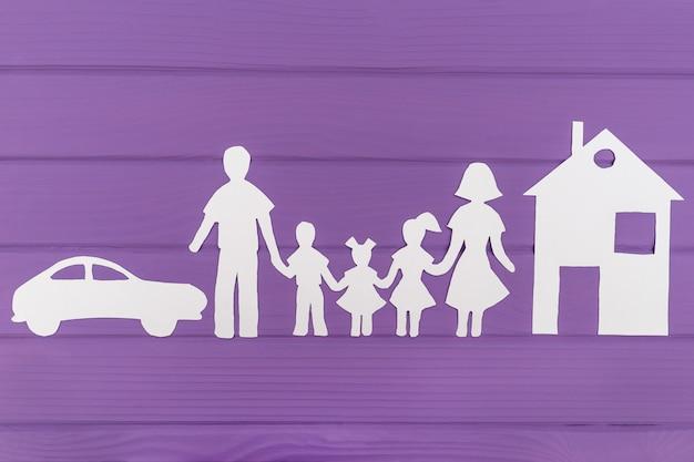 De silhouetten gesneden uit papier van man en vrouw met twee meisjes en jongen huis en auto in de buurt