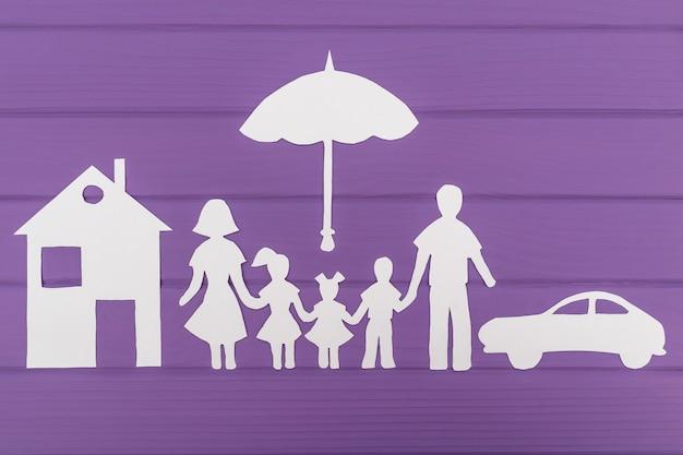 De silhouetten gesneden uit papier van man en vrouw met twee meisjes en jongen onder de paraplu, huis en auto in de buurt