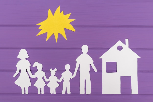 De silhouetten gesneden uit papier van man en vrouw met twee meisjes en jongen onder de zon, huis in de buurt