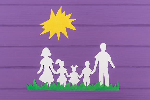 De silhouetten gesneden uit papier van man en vrouw met twee meisjes en jongen op het gras onder de zon