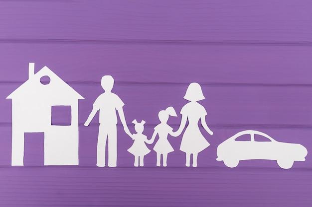 De silhouetten gesneden uit papier van man en vrouw met twee meisjes, huis en auto in de buurt