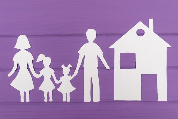 De silhouetten gesneden uit papier van man en vrouw met twee meisjes, huis in de buurt