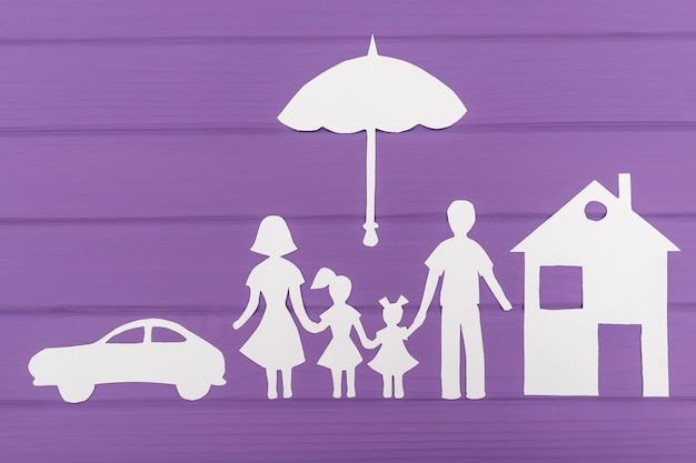 De silhouetten gesneden uit papier van man en vrouw met twee meisjes onder de paraplu, huis en auto in de buurt