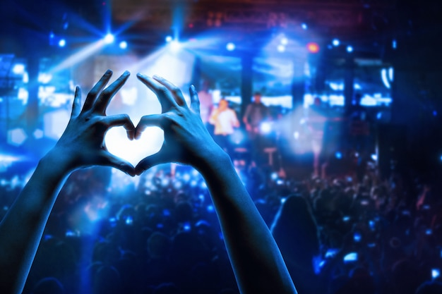 De silhouetten van concertmenigte voor felle podiumverlichting. concert van een abstracte rockband