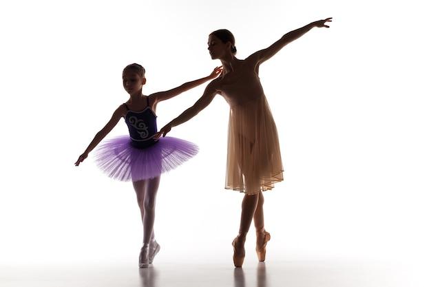 De silhouetten van kleine ballerina en persoonlijke klassieke balletleraar in dans