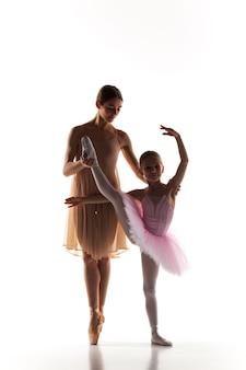 De silhouetten van kleine ballerina en persoonlijke klassieke balletleraar in dansstudio dansen op een witte achtergrond
