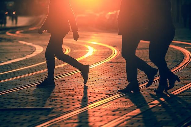 De silhouetten van mensen die op stadsstraat lopen en schaduwen op bestrating met spoorwegsporen gieten in bordeaux, korreltextuur zijn van toepassing