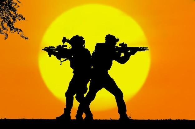 De silhouetten van twee legersoldaten op een oranje zonsondergangachtergrond