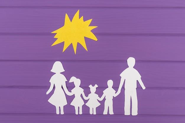 De silhouetten zijn uit papier gesneden van man en vrouw met twee meisjes en een jongen onder de zon