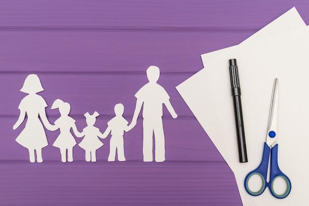 De silhouetten zijn uit papier gesneden van man en vrouw met twee meisjes en een jongen