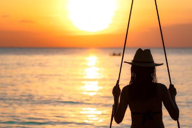 De silhouetvrouw draagt bikini en de strohoed slingert de schommels bij het strand op de zomervakantie bij zonsondergang