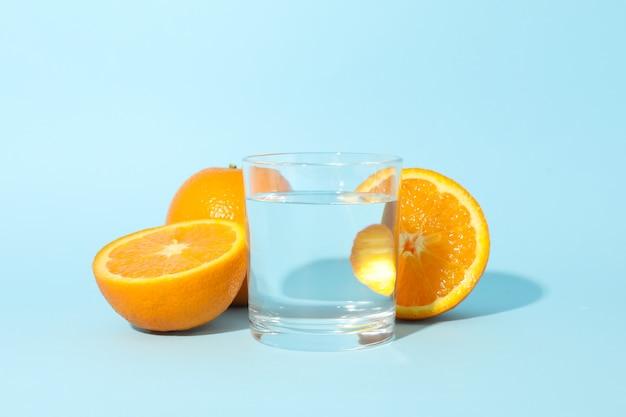 De sinaasappel en het glas water op blauw, sluiten omhoog