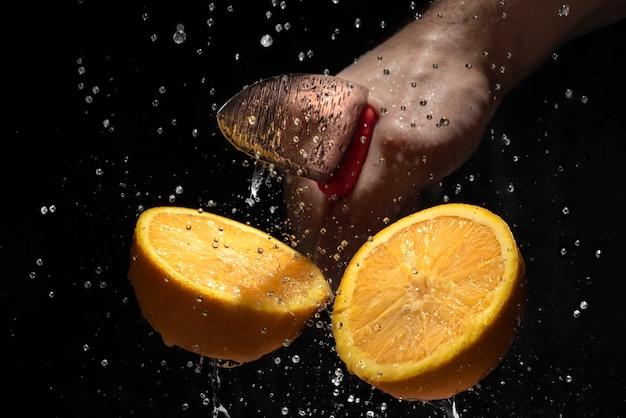 De sinaasappel gehakt met een mes op een donkere achtergrond.