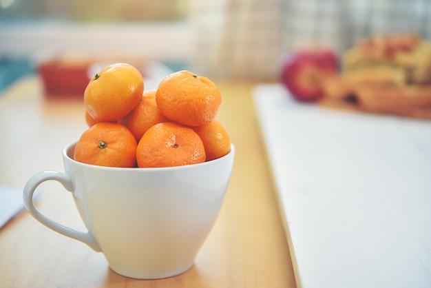 De sinaasappel is in de beker klaar om een onderdeel van het voedsel te zijn.