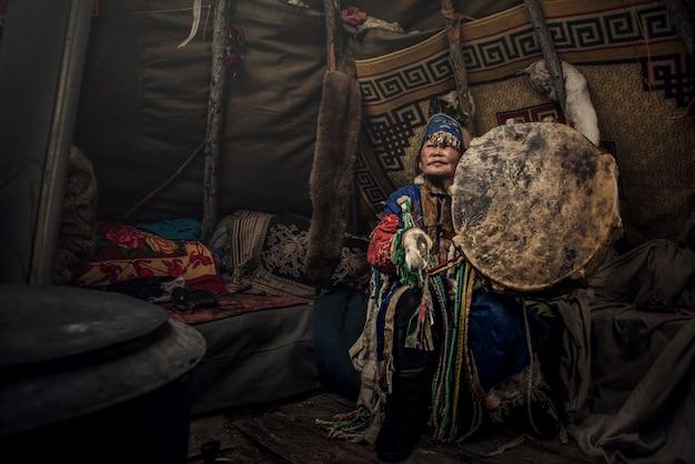 De sjamaan uit mongolië doet een authentiek ritueel van het oproepen van geesten