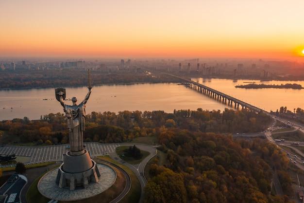 De skyline van kiev over prachtige vurige zonsondergang, oekraïne. monument moederland.