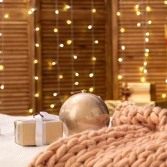 De slaapkamer is ingericht voor kerstmis. het bed is bedekt met een zachte merino grote gebreide deken. de muren zijn versierd met lichten van slingers. gezellige zachte sfeer van de lodge of love