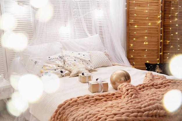 De slaapkamer is ingericht voor kerstmis. het bed is bedekt met een zachte merino grote gebreide deken.