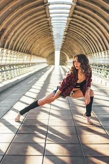 De slanke jonge donkerbruine turner van de vrouwenstraatdanser zit in spleten stelt op straatbrug