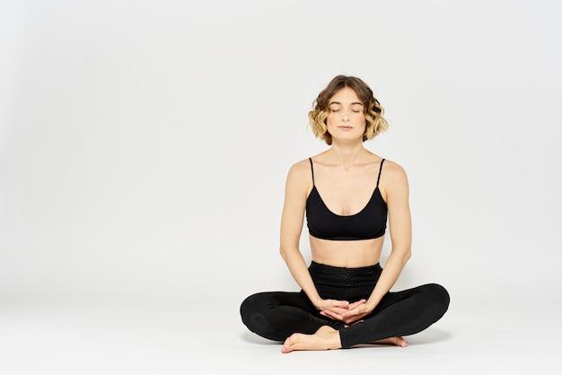 De slanke jonge vrouw oefent yoga en oefeningen thuis in de studio uit